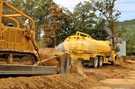compacting: A water truck sprays water on a fresh fill layer of soil and rock for a new road construciton project.