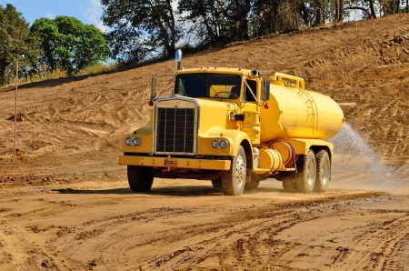 wetting: A water truck sprays water on a fresh fill layer of soil and rock for a new road construciton project.