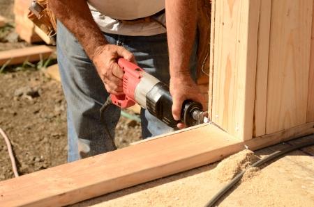 새 집 건설 프로젝트에 1 층 벽의 기지 판에 문을 잘라 왕복 톱을 사용 하여 계약자 노동자를 구축 스톡 콘텐츠