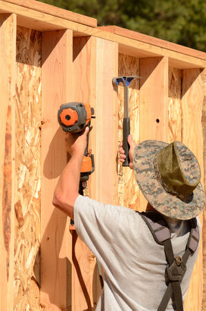 Building contractor worker putting in a interior wall partition nailer wall for the first floor on a new home construciton project