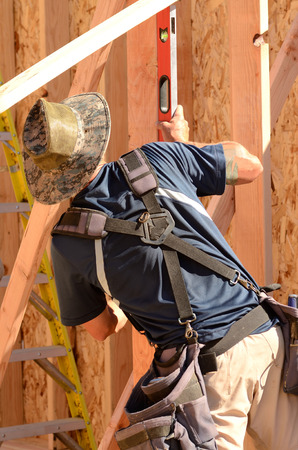 plumb: Building contractor worker using a long level to plumb the walls for the first floor on a new home construciton project Stock Photo