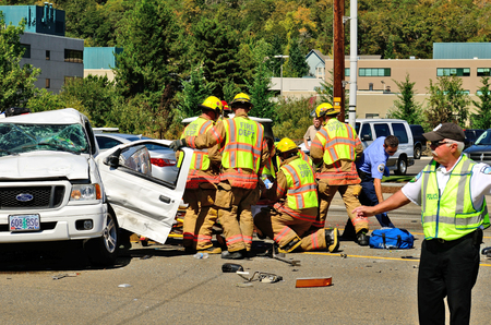 Firefighters and paramedics extricate the victims of a two vehicle t-bone type accident at an intersection resulted in major jinjuries due to failure to obey stopping sign in Roseburg, Oregon on September 11, 2013