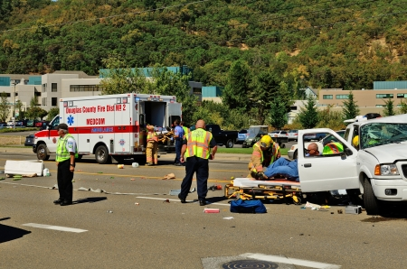 resulted: Firefighters and paramedics extricate the victims of a two vehicle t-bone type accident at an intersection resulted in major jinjuries due to failure to obey stopping sign in Roseburg, Oregon on September 11, 2013 Editorial