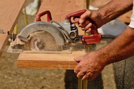 Aannemer werknemer met de hand gehouden wormaandrijving cirkelzaag op platen gesneden op een nieuw huis construciton project Stockfoto