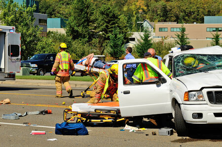 rescuing: Firefighters and paramedics extricate the victims of a two vehicle t-bone type accident at an intersection resulted in major jinjuries due to failure to obey stopping sign in Roseburg, Oregon on September 11, 2013 Editorial