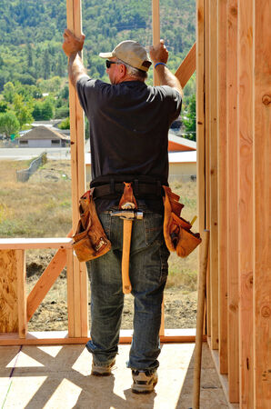 second floor: Building contractor worker using a wall jack to raise a wall for the second floor on a new home construciton project Stock Photo