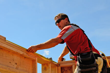 Building contractor worker measuring out the top plate of the wall in preparation for the rafter on the second floor on a new home construciton project