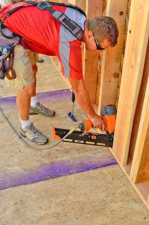 second floor: Building contractor worker using a air nail gun to attach the wall for the second floor on a new home construciton project