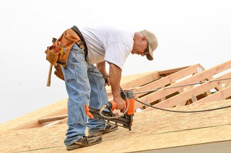 Framing aannemer installeren dakplaten boven balken op een nieuwe commerciële woningbouw project