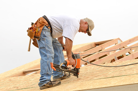 construction project: Framing contractor installing roof sheeting over rafters on a new commercial residential construction project Stock Photo