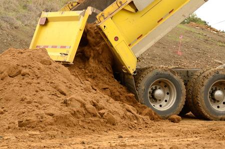 Tien yard dump truck leveren van een lading van vuil voor een vulling project bij een nieuwe commerciële ontwikkeling bouwproject Stockfoto