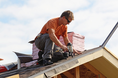 roof shingles: Building contractor putting the asphalt roofing on a large commercial apartment building development Stock Photo