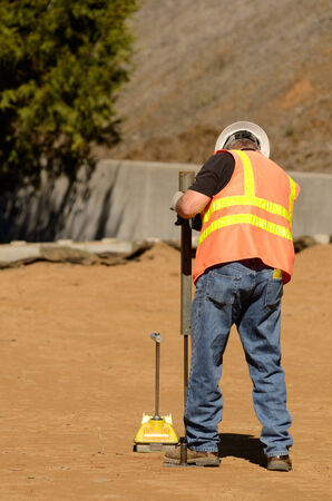 Field engineer using a Nuclear Density Gauge to check for soil density of a soil lift fill on a new commercial development construction project