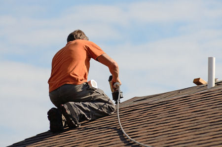 shingles: Building contractor putting the asphalt roofing on a large commercial apartment building development Stock Photo