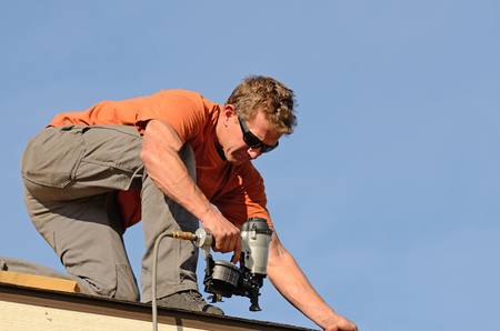 Building contractor putting the asphalt roofing on a large commercial apartment building development Stok Fotoğraf