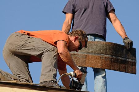 Bouwondernemer zetten het asfalt dakbedekking op een grote commerciële appartementencomplex ontwikkeling