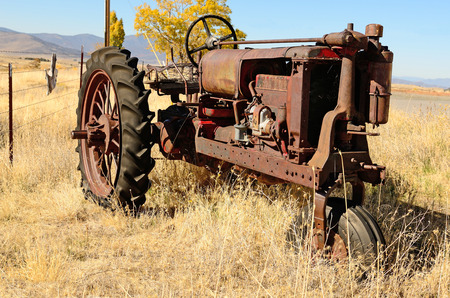 An old three wheel tractor sits next to a large cattle ranch in northern California Stock Photo - 26132389
