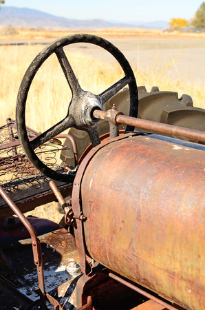 meta: An old three wheel tractor sits next to a large cattle ranch in northern California