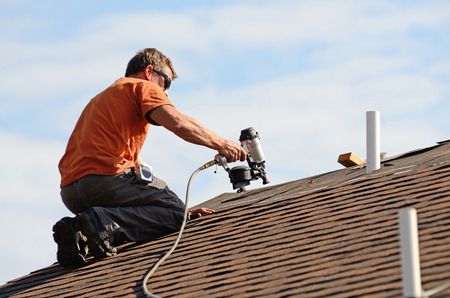 shingle: Building contractor putting the asphalt roofing on a large commercial apartment building development Stock Photo