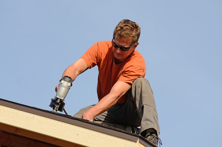 Building contractor putting the asphalt roofing on a large commercial apartment building development 写真素材
