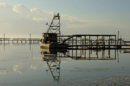 shrimp boat: Old shrimp boat sits a dock in the early morning in Corpus Christi Bay, Texas
