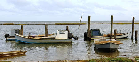 shrimp boat: Small fishing boats sit in a marsh area off of the Gulf of Mexico near Pensacola Florida Stock Photo