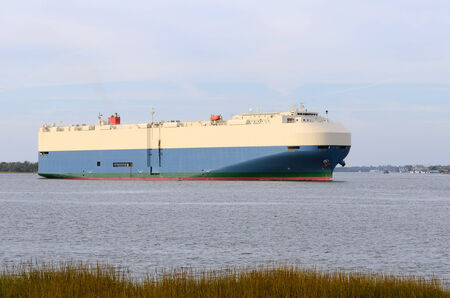 car retailer: A large ship or barge built specifically for transporting automobiles leaves port near Brunswick Georgia Stock Photo