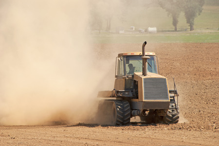 Agricutlural tractor pulling a cultipacker to break down the soil for final preparation before planting