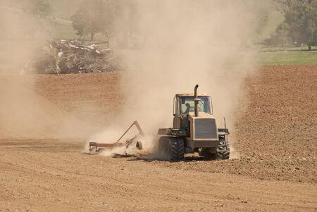 Agricutlural Traktor zieht einen cultipacker bis zur abschließenden Vorbereitung vor dem Pflanzen brechen die Boden Standard-Bild - 27822617