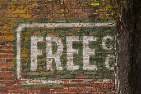 faded: Old sign Free Service  painted on a brick wall of a building on main street in Yoncalla Oregon