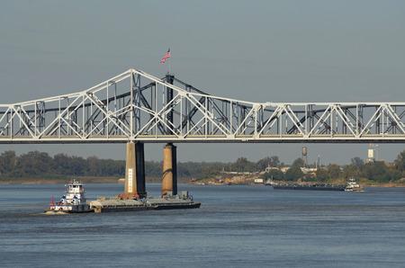 petrolium: Tug boat and barges of petrolium oil passes under the Vicksburg Bridge along the Mississippi River