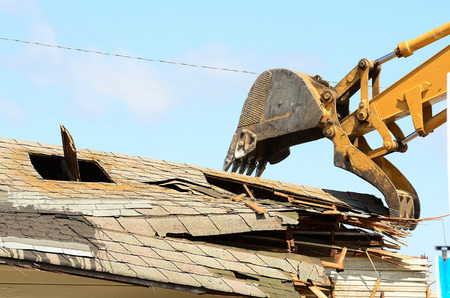 tearing down: A large track hoe excavator tearing down an old hotel to make way for a new commercial development
