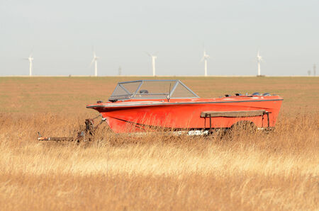 A old red pleasure boat sits in a field of grass in the northeastern plains of Texas photo