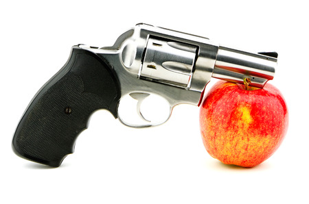 sidearm: Pistol and apple studio concept shot for guns and school violence, mild relationship also guns and health