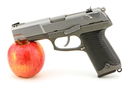 gun barrel: Pistol and apple studio concept shot for guns and school violence, mild relationship also guns and health