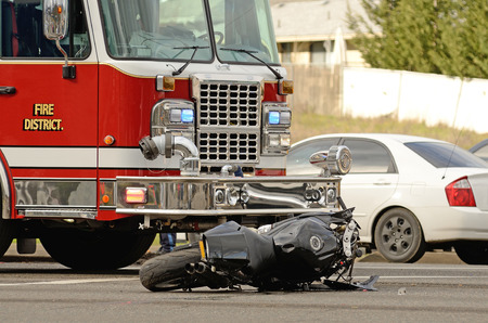 motorcycle accidents: ROSEBURG, OR, USA - JANUARY 13, 2014:  Emergeny responders at the scene of a motorcycle vs car at a busy intersection that left the rider with serious injuries.