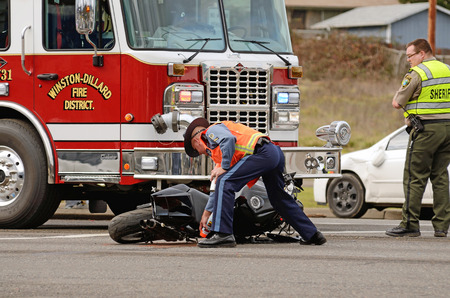 ROSEBURG, OR, USA - JANUARY 13, 2014:  Emergeny responders at the scene of a motorcycle vs car at a busy intersection that left the rider with serious injuries.