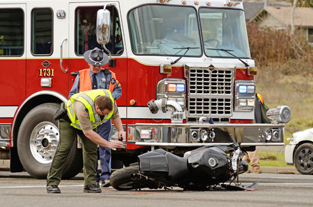 motorcycle officer: ROSEBURG, OR, USA - JANUARY 13, 2014:  Emergeny responders at the scene of a motorcycle vs car at a busy intersection that left the rider with serious injuries.