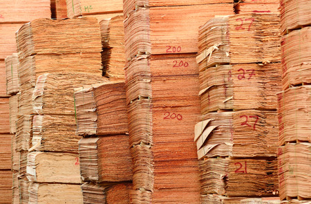 Stack of douglas fir veneer sits outside a mill that produces plywood panels 版權商用圖片