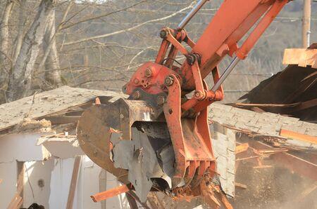 Une pelle piste houe en utilisant sa griffe pouce pour abattre un vieil hôtel à faire place à un nouveau développement commercial