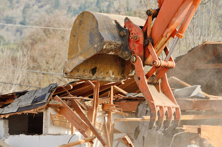 A track hoe excavator using its claw thumb to tear down an old hotel to make way for a new commercial development