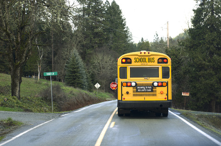 A school bus stops on a rural road to let off students