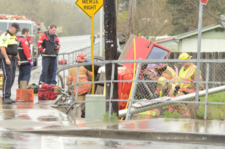 rescuing: Roseburg OR - March 2013  Emergency workers extricate a victim from a single car, rollover accident during a spring rain in Roseburg Oregon, March 19, 2013 Editorial