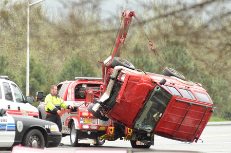 Roseburg OR - March 2013: A tow truck lifts a car following a rollover accident during a spring rain in Roseburg Oregon, March 19, 2013