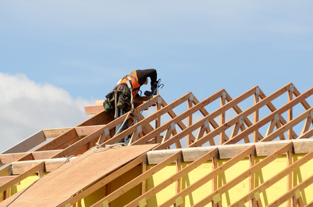 construction crew: Construction crew working on the roof sheeting and outriggers or ladder of a new, two story, commercial appartment building in Oregon Stock Photo