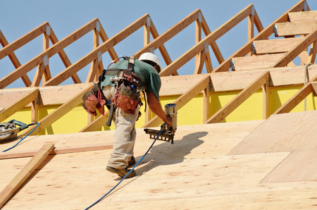 Construction crew working on the roof sheeting of a new, two story, commercial appartment building in Oregon Stock Photo