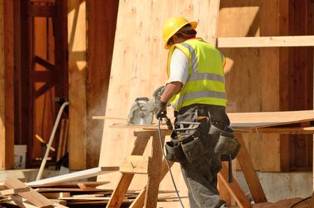 alba�il: Equipo de construcci�n con una sierra el�ctrica en el revestimiento de tejados de una nueva, de dos pisos, apartamento edificio comercial en Oregon Foto de archivo