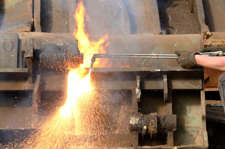 salvage yards: A worker uses a oxygen acetylene cutting torch to cut a large metal object into managable pieces at a metal recycling plant Stock Photo