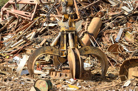 salvage yard: Large magnet attached to a track hoe excavator at a metal recycling plant