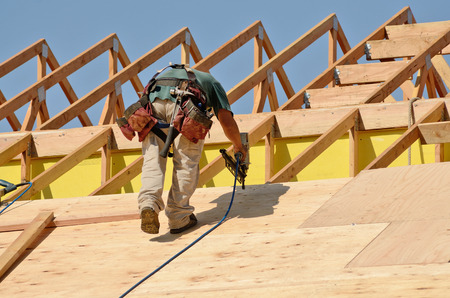 construction safety: Construction crew working on the roof sheeting of a new, two story, commercial appartment building in Oregon Stock Photo
